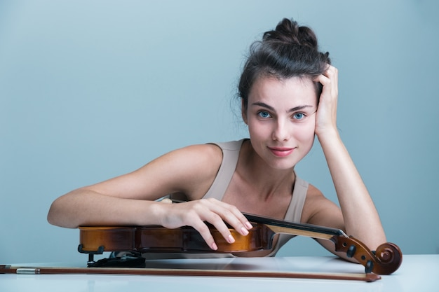 Portret pięknej młodej kobiety siedzącej przy stole ze skrzypcami na białym tle na niebieskim tle