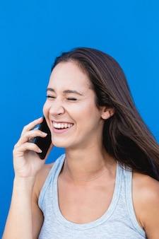 Portret pięknej młodej kobiety, śmiejąc się i rozmawiając przez telefon z niebieską ścianą