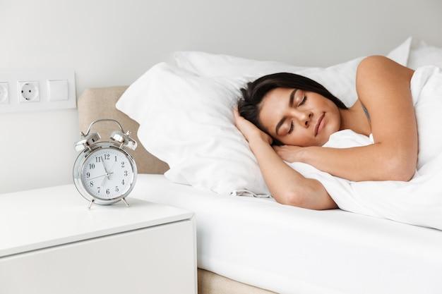 Portret pięknej młodej kobiety spanie w łóżku w sypialni, z budzikiem na szafce nocnej