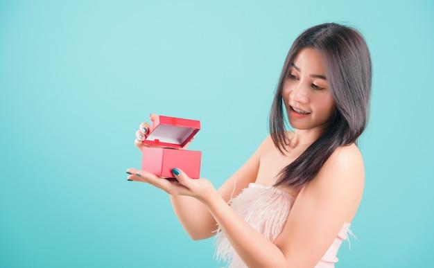Portret pięknej młodej kobiety stojącej uśmiech otwierający czerwone pudełko, urodziny niespodzianka