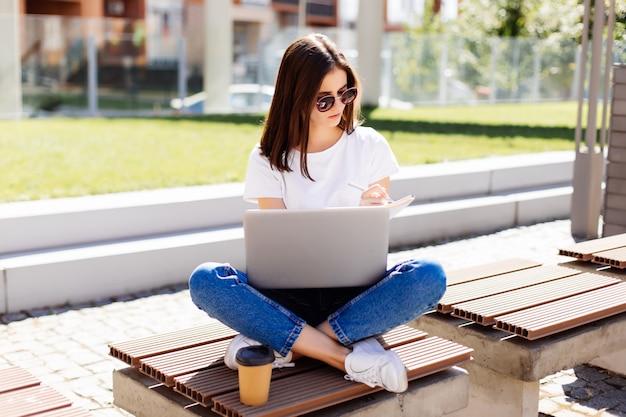 Portret pięknej młodej kobiety student studiuje na swoim laptopie i pisze notatki w zeszycie siedząc na ławce w parku z filiżanką kawy