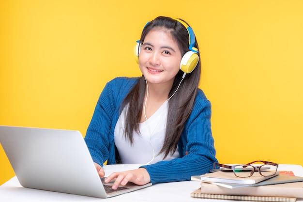 Portret pięknej młodej kobiety studiującej w domu przy stole z laptopem i notebookiem - nauka w systemie e-learningowym online
