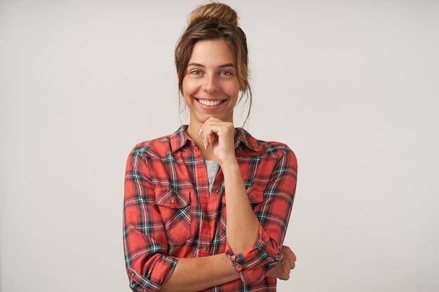 Portret pięknej młodej kobiety szczęśliwy z naturalnym makijażem, trzymając podniesioną rękę na brodzie i uśmiechając się wesoło do kamery, pozując na białym tle