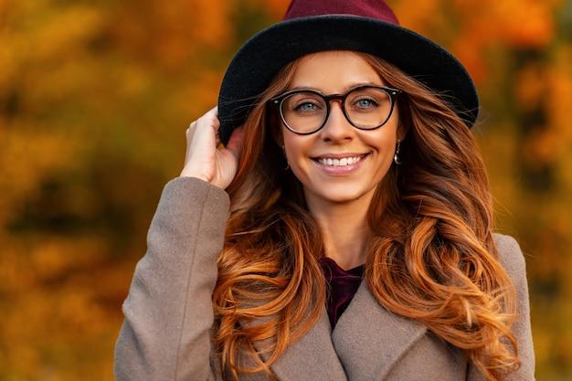 Portret pięknej młodej kobiety szczęśliwy z pięknym uśmiechem w eleganckim kapeluszu w stylowych okularach w modnym płaszczu w parku. wesoła hipster dziewczyna w modnej odzieży wierzchniej pozuje w jesiennym lesie