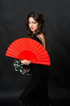 Portret pięknej młodej kobiety tańczącej flamenco z wentylatorem w studio