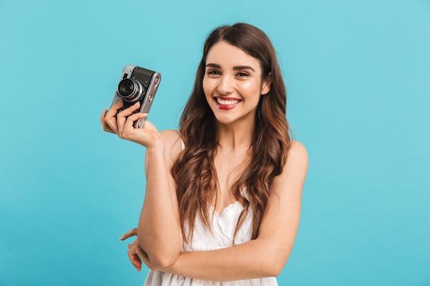 Portret pięknej młodej kobiety trzymającej aparat fotograficzny