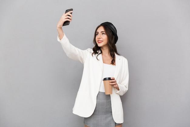 Portret pięknej młodej kobiety ubranej w kurtkę na szarym tle, trzymając filiżankę kawy, biorąc selfie z telefonem komórkowym