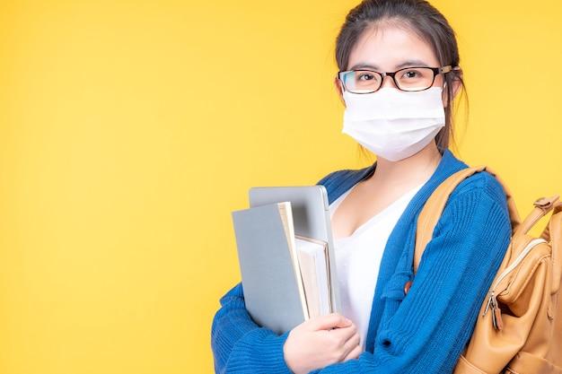 Portret pięknej młodej kobiety uczennicy w masce trzymającej podręcznik - studiuje on-line system e-learningowy