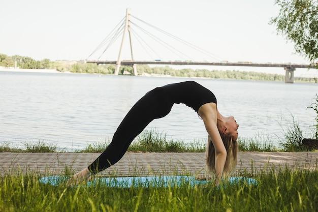 Portret pięknej młodej kobiety uprawiania jogi na świeżym powietrzu w parku. piękna dziewczyna w czarnym garniturze chudy.