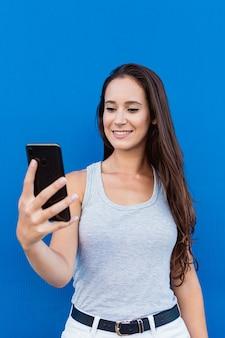 Portret pięknej młodej kobiety, uśmiechając się i używając smartfona z niebieską ścianą w tle