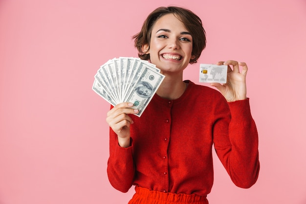 Portret pięknej młodej kobiety w czerwonych ubraniach stojących na białym tle na różowym tle, pokazując banknoty, trzymając kartę kredytową