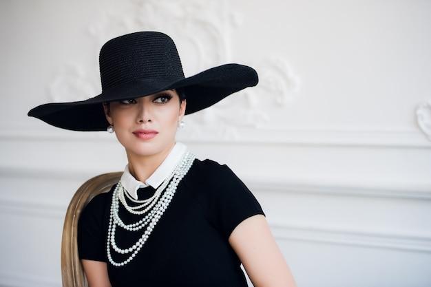 Portret pięknej młodej kobiety w eleganckim czarnym kapeluszu w stylu retro