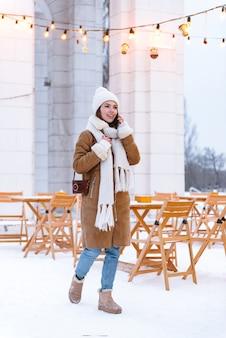 Portret pięknej młodej kobiety w kapeluszu i szaliku spaceru na świeżym powietrzu w zimie, rozmawiając przez telefon komórkowy.