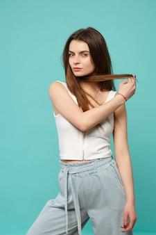 Portret pięknej młodej kobiety w lekkich ubraniach dorywczo patrząc kamery, trzymając włosy na białym tle na niebieskim tle turkusu w studio. ludzie szczere emocje, koncepcja stylu życia. makieta miejsca na kopię.