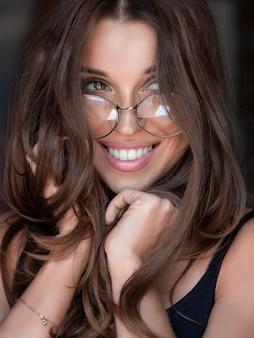 Portret pięknej młodej kobiety w okularach. uśmiecha się i odwraca wzrok.