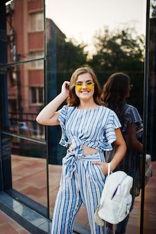 Portret pięknej młodej kobiety w pasiasty kombinezon i żółte okulary pozowanie