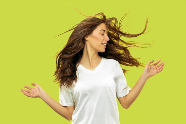 Portret pięknej młodej kobiety w połowie długości na białym tle. modelka wygląda na szczęśliwą, uśmiechniętą i tańczącą. wyraz twarzy, koncepcja ludzkich emocji, uroda i opieka zdrowotna.