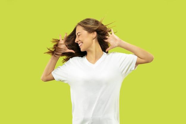 Portret pięknej młodej kobiety w połowie długości na białym tle na zielonej przestrzeni. modelka wygląda na szczęśliwą, uśmiechniętą i tańczącą