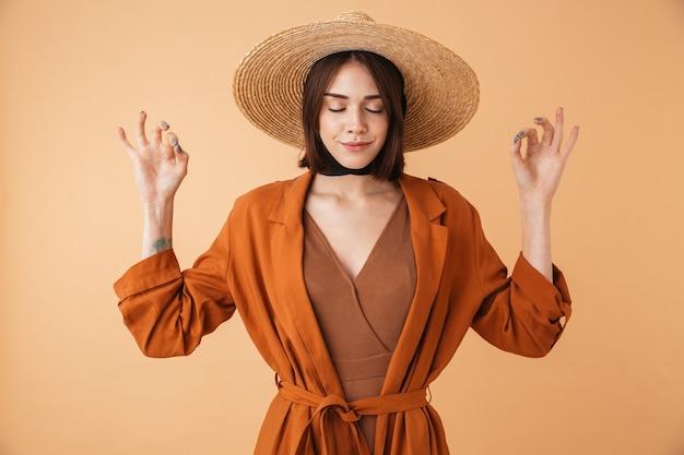 Portret pięknej młodej kobiety w słomkowym kapeluszu stojącej na białym tle nad beżową ścianą, medytującej