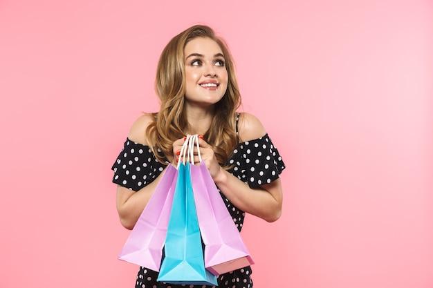 Portret pięknej młodej kobiety w sukience stojącej na tle różowej ściany, niosącej torby na zakupy
