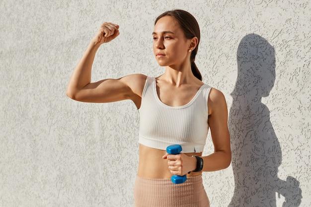 Portret pięknej młodej kobiety w wieku brunetki, ubranej w biały top, trzymającej w ręku niebieski hantle, pokazującej bicepsy, dumnej ze swoich mięśni, odwracającej wzrok.