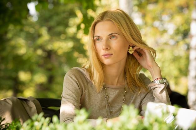 Portret pięknej młodej kobiety w wiosennym parku. zdjęcia w ciepłych kolorach