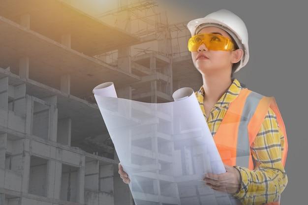 Portret pięknej młodej kobiety z azji, inżynier budownictwa, trzymający rysunek z przodu