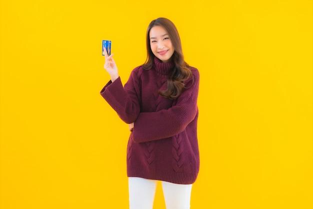 Portret pięknej młodej kobiety z azji kartą kredytową na zakupy online