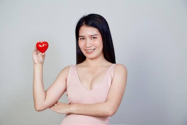 Portret pięknej młodej kobiety z azji, wskazując kształt czerwone serce na białym tle na jasnoszarym tle z miejsca kopiowania