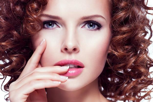 Portret pięknej młodej kobiety z brunetka kręcone włosy pozowanie studio. zbliżenie twarzy z kręcone fryzury, na białym tle.