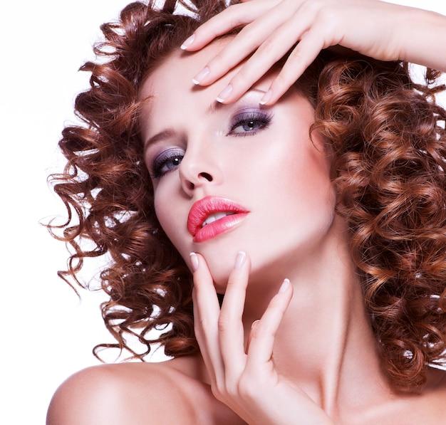 Portret pięknej młodej kobiety z brunetka kręcone włosy pozowanie zbliżenie twarzy z kręcone fryzury, na białym tle.
