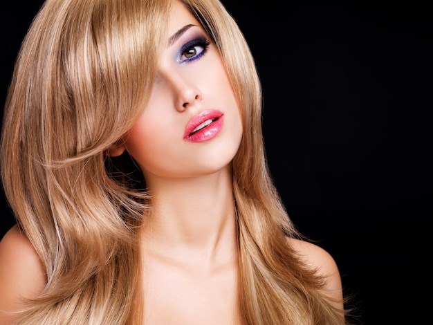 Portret pięknej młodej kobiety z długimi białymi włosami i czerwonymi ustami. modelka pozowanie na czarno