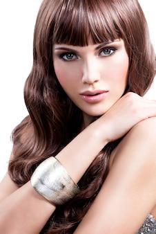 Portret pięknej młodej kobiety z długimi brązowymi włosami. śliczna modelka ze stylową biżuterią w srebrnym kolorze.