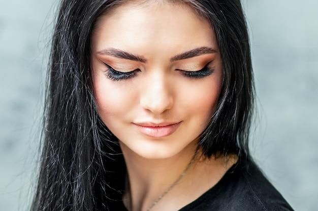 Portret pięknej młodej kobiety z długimi rzęsami i pięknym makijażem.