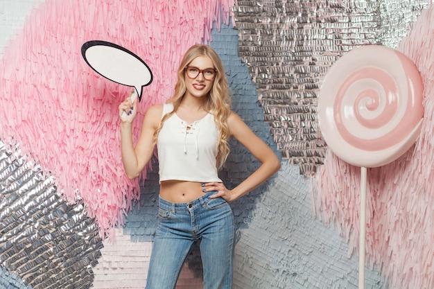 Portret pięknej młodej kobiety z długimi włosami blondie w okularach, trzymając dymek