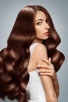 Portret pięknej młodej kobiety z długimi włosami patrząc. kosmetyki do włosów, pielęgnacja włosów.