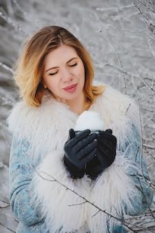 Portret pięknej młodej kobiety z filiżanką śniegu w rękach.