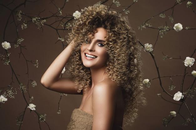 Portret pięknej młodej kobiety z fryzurą afro i pięknym makijażem z dużą ilością białych kwiatów na ścianie