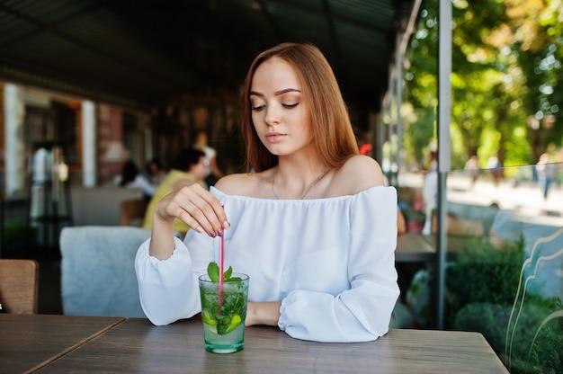 Portret pięknej młodej kobiety z koktajl mojito w kawiarni obok parku.