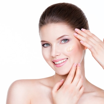 Portret pięknej młodej kobiety z kosmetycznym podkładem na skórze - na białym tle.