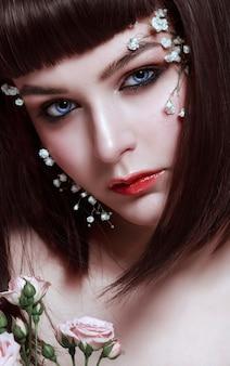 Portret pięknej młodej kobiety z kwiatami na jej twarzy. makijaż w stylu koreańskim, piękna lalka