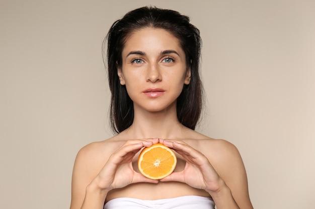 Portret pięknej młodej kobiety z naturalnym makijażem i pomarańczą na jasnym tle