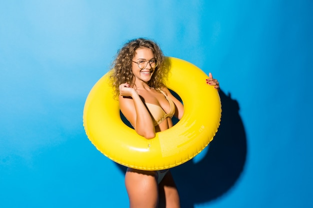 Portret pięknej młodej kobiety z okularami przeciwsłonecznymi w bikini, grając z żółtym nadmuchiwanym pierścieniem na białym tle na niebieskiej ścianie