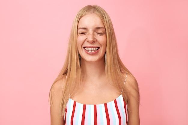 Portret pięknej młodej kobiety z piegami, kolczykiem na twarzy i aparatem ortodontycznym, uśmiechnięta podekscytowana, z zamkniętymi oczami, czekająca na niespodziankę