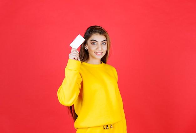 Portret pięknej młodej kobiety z pustą wizytówką stojącą