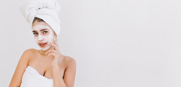 Portret pięknej młodej kobiety z ręcznikami po kąpieli zrobić maseczkę kosmetyczną na jej twarzy.