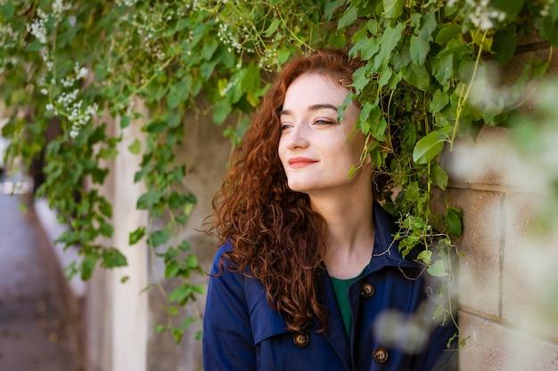 Portret pięknej młodej kobiety z rudymi włosami i piegami na ścianie i zieleni