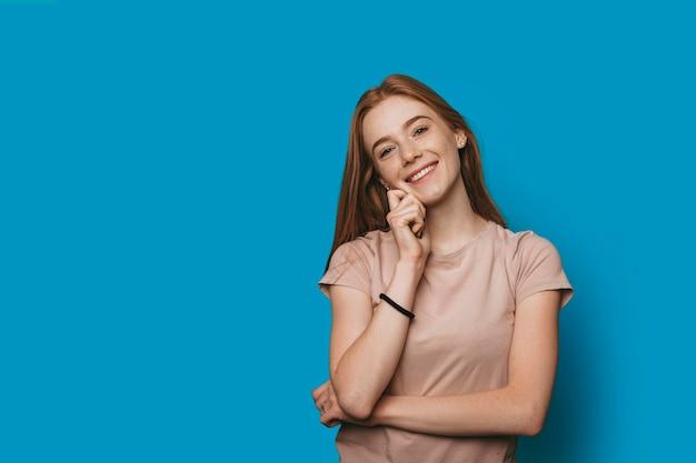 Portret pięknej młodej kobiety z rudymi włosami z piegami patrząc na kamery, śmiejąc się, dotykając jej twarzy na ścianie w niebieskim studio.