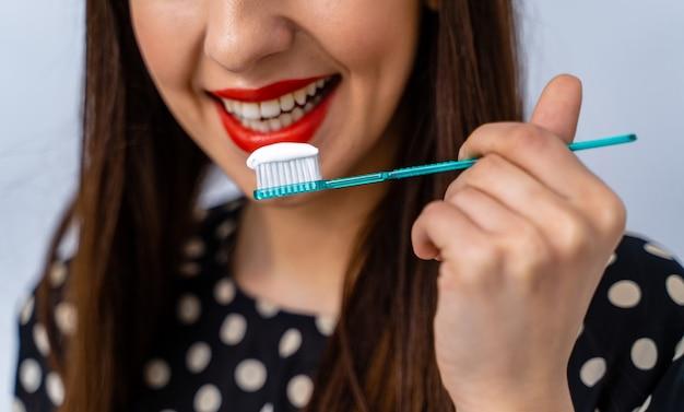 Portret pięknej młodej kobiety z szczoteczką do zębów w ręce. zdrowe, białe zęby. koncepcja dentystyczna.