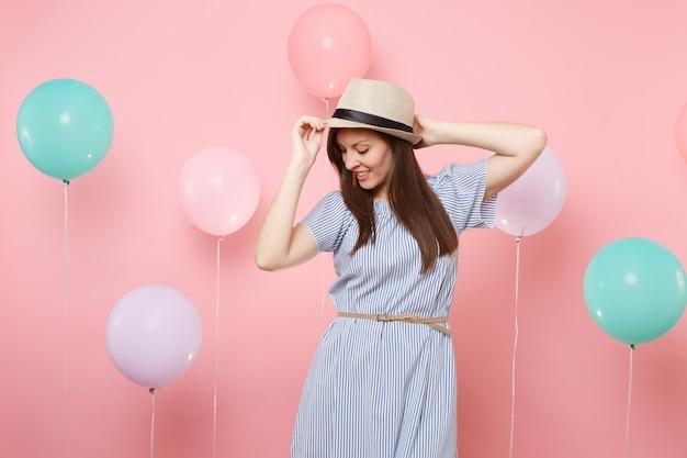 Portret pięknej młodej kobiety z zamkniętymi oczami w słomkowym letnim kapeluszu i niebieskiej sukience na pastelowym różowym tle z kolorowymi balonami. urodziny wakacje party ludzie szczere emocje koncepcja.